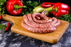 Fresh raw sausage on wooden board, Raw barbecue sausages with spices and vegetables. Top view Freshly made raw breed butchers sausages. Free space for your text