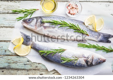 Fresh raw seabass and ingredients for cooking. Two fish seabass with lemon, spices and herbs on wooden table, top view with copy space.