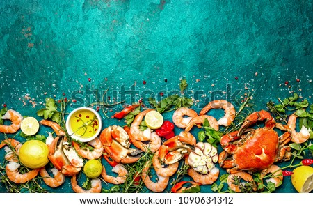 Fresh raw seafood - shrimps and crabs with herbs and spices on turquoise background. Copy space.