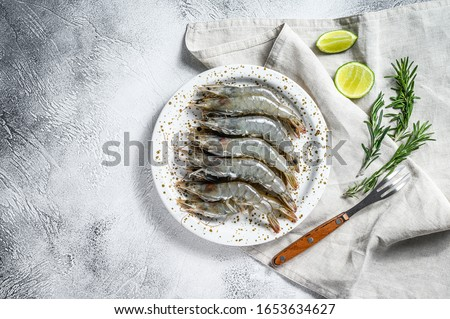 Fresh raw tiger prawns, shrimps and spices on a white plate. Gray background. Top view. Copy space Stockfoto ©