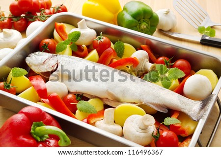Fresh raw trout with raw vegetables in a casserole ready to be baked