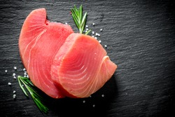 Fresh raw tuna steak with rosemary. On black rustic background