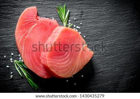 Fresh raw tuna steak with rosemary. On black rustic background Foto d'archivio ©