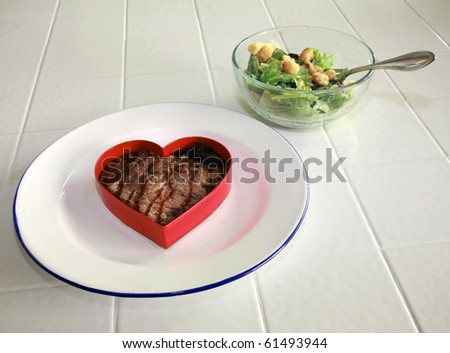 fresh raw USDA beef steak cut into a heart shaped on a plate