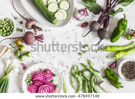 Fresh raw vegetables - beets, green peas and beans, zucchini, peppers, onions, garlic, spices on a light background. Cooking background, space for text. Top view