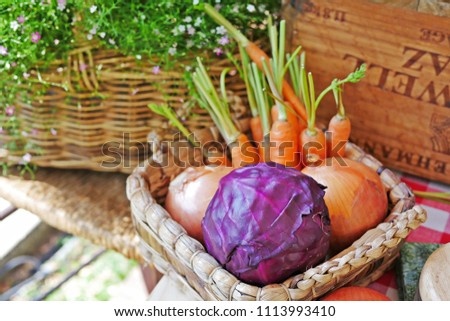 Fresh, raw vegetables for cooking:carrots and onions in a basket with flowers background. Selective focus. Selective focus. Close up. #1113993410