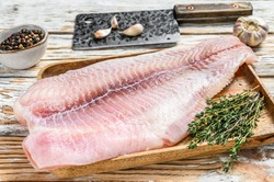 Fresh raw white fish fillet catfish with spices. White wooden background. Top view.
