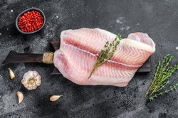 Fresh raw white fish fillet Pangasius with spices. Black background. Top view