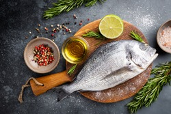 Fresh ready to cook raw bream fish dorado with ingredients and seasonings like rosemary, salt, pepper, lime and olive oil, top view