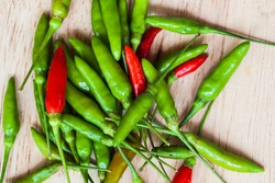 fresh red and green chilli on old wood background. guinea pepper ; bird pepper ; bird-chilli ; small capsicum ; chilli pepper ; tiny fiery chilli ; hot chilli .
