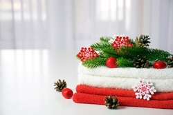 Fresh red and white towels folded on the table, fir branches, snowflakes and pine cones with tulle window on background. New year cozy home interior. Christmas spa or beauty salon concept. Copy space