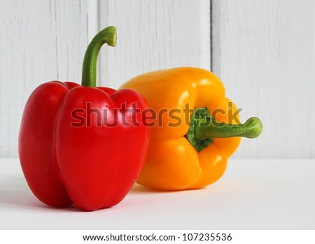 Fresh red and yellow bell peppers (Capsicum) against a white wood background