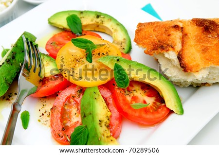 Fresh red and yellow tomatoes, sliced avocado, basil leaves and raspberry vinaigrette dressing on a square white plate and piece of artisan bread