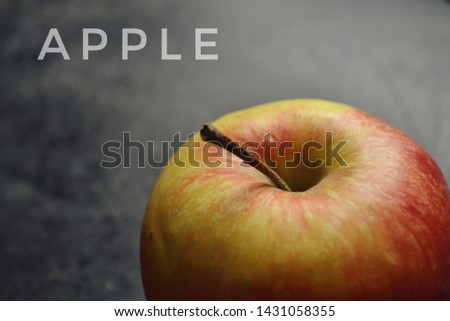 Fresh red apple. Juicy fruit. The inscription on the pictures of an apple. Fruit background. Apple closeup isolated on a black and grey background.