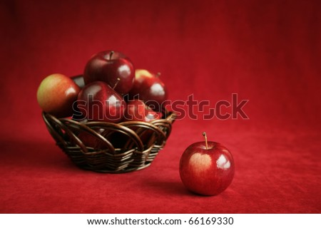 fresh red apple with a basket full of red apple in background