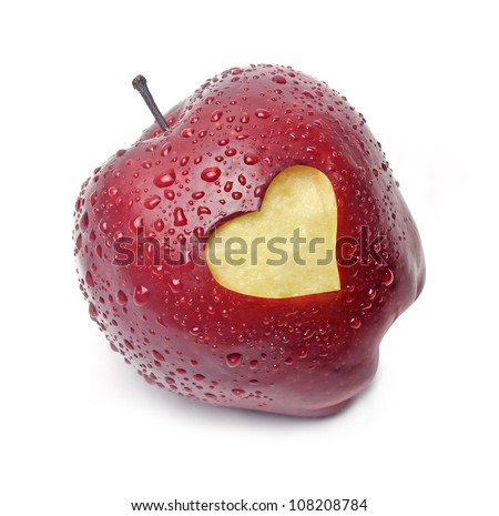 Fresh red apple with a heart shaped cut-out on white background