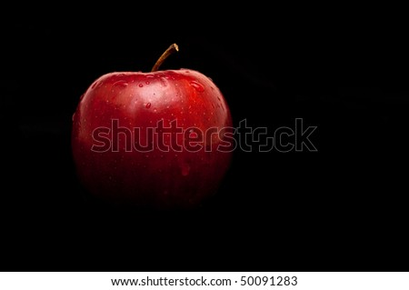 fresh red apple with droplets of water against black background