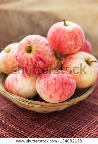 Fresh red apples in basket on the table and wooden background - stock photo