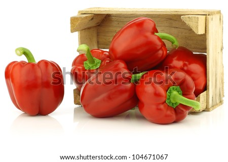 fresh red bell peppers (capsicum) in a wooden crate on a white background
