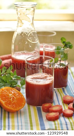 Fresh red carrot juice being poured surrounded by fresh fruits and vegetables and mint leaves