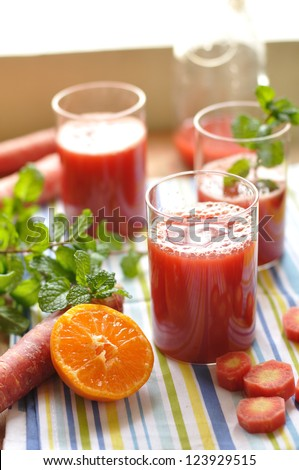 Fresh red carrot juice surrounded by fresh fruits and vegetables and mint leaves
