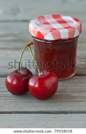 fresh red cherries and jar of cherries jam on the wooden table