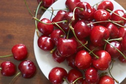 Fresh red cherries fruit on plate on wooden background close up. High quality photo