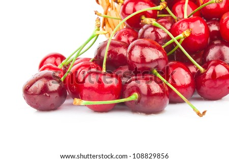 Fresh red cherries in wicker basket isolated on white background