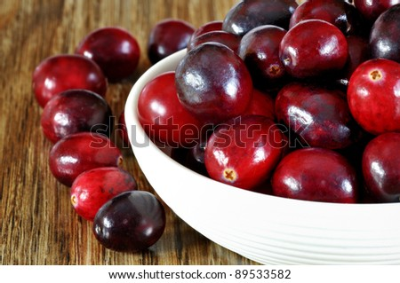 Fresh red cranberries in bowl on wooden background, selective focus