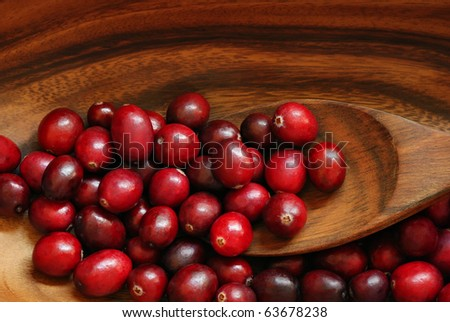 Fresh red cranberries in wooden bowl with spoon.  Macro with shallow dof.
