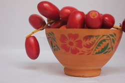Fresh Red Dates in a Clay Bowl, White Background, Selective Focus, Clay Bowl with Red Flower and Green Leaf