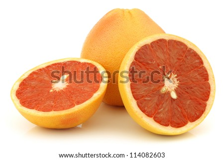 fresh red grapefruit and a cut one on a white background