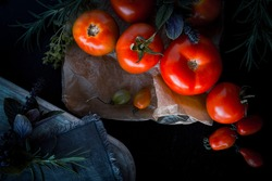 Fresh red , green and  yellow  tomatoes  on a black  background. Dark moody artistic style. Top view, selective focus, close up, copy space.