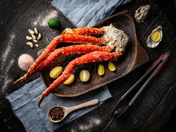 Fresh red king crab crab claws with lemon slices and spices . Tasty kamchatka crab's claw