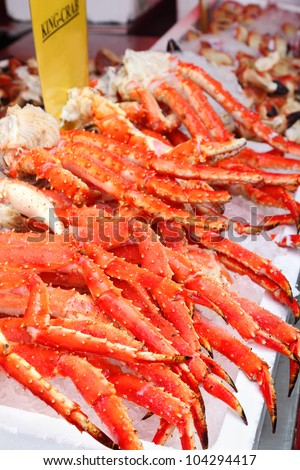 Fresh red king-crab legs in ice at seafood market; cabs high content protein and low calorie