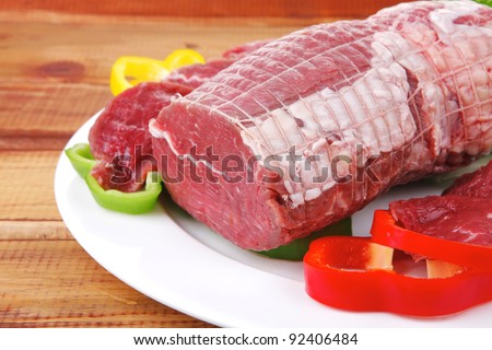 fresh red meat with vegetables on wood