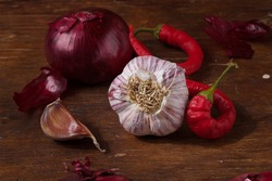 Fresh red onions, garlic, hot chilli pepper on wooden brown kitchen table. Seasonings, spices, flavourings on rustic country background.