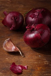 Fresh red onions, garlic on wooden brown kitchen table. Seasonings, spices, flavourings on rustic country background. Vertical shot