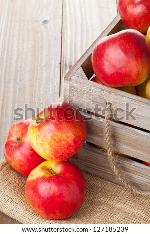 Fresh red organic apples in wooden crate on table