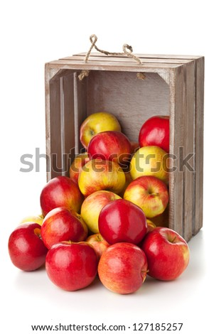 Fresh red organic apples in wooden crate on white background