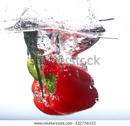 Fresh red paprika falling into the water with a splash of water. On a white background