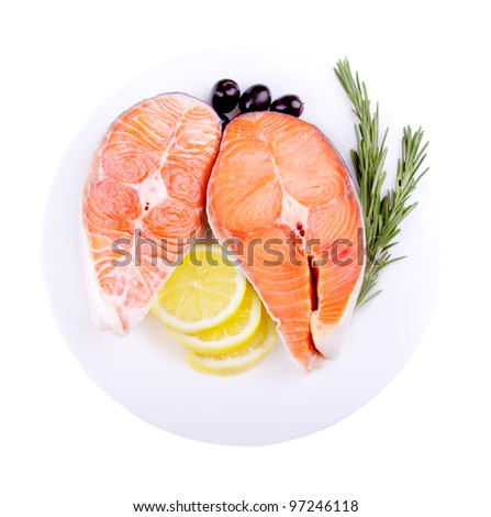 Fresh red salmon fish steak with rosemary lemon and olives