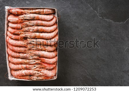 Fresh red shrimps or prawn packing in box on slate stone background. Seafood, top view, flat lay, copy space