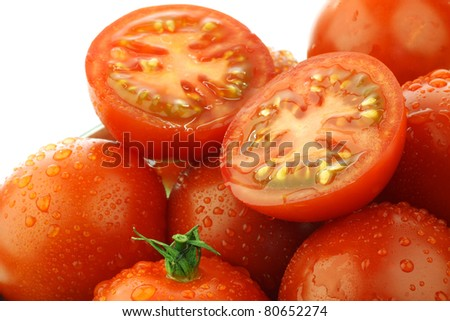 fresh red tomatoes and two halves with water droplets on a white background - stock photo