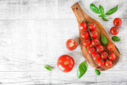 Fresh red tomatoes on white background or light rustic table. Tomato variety vegetable concept space for text or banner top view