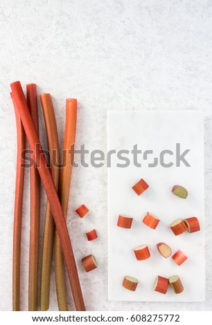 Fresh rhubarb and cut pieces of rhubarb on white marble chopping board.