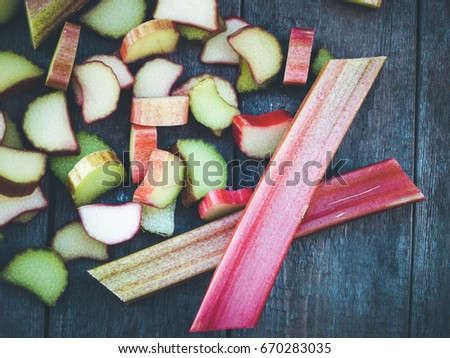 Fresh rhubarb on wooden table, selective focus and toned image