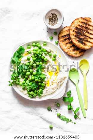 Fresh ricotta cheese with green peas, olive oil, pepper and herbs on a light background, top view. Healthy diet food - delicious breakfast, snack, appetizers.Flat lay     Foto d'archivio ©