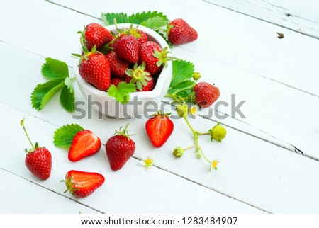 fresh ripe and under ripe strawberry fruits, flowers, leaves on white wood table background #1283484907