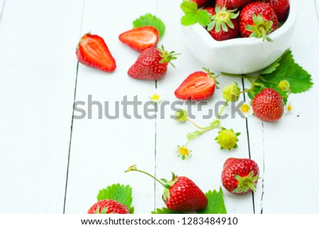fresh ripe and under ripe strawberry fruits, flowers, leaves on white wood table background #1283484910